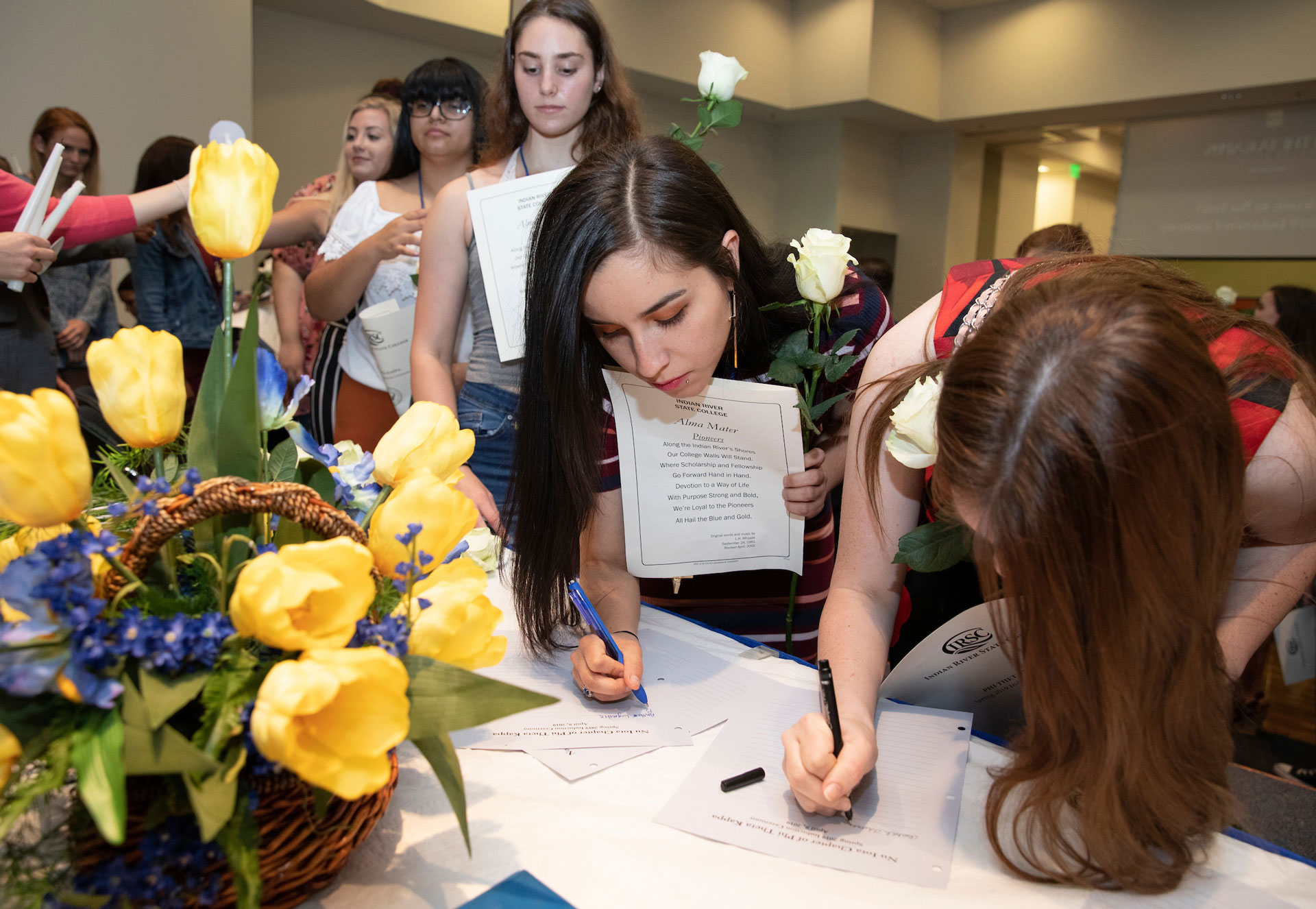 Inductees into the Nu Iota Chapter of Phi Theta Kappa sign the chapter's member registiry.